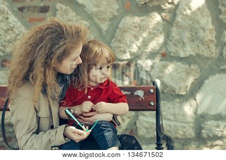 Little Boy And Woman On The Bench