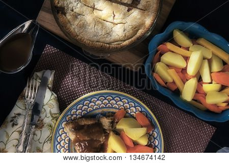 Rabbit pie with a side of root vegetables and gravy.