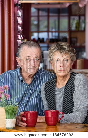 Serious Mature Couple In Coffee House
