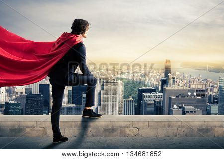 Businessman with a superhero cape view from above the city