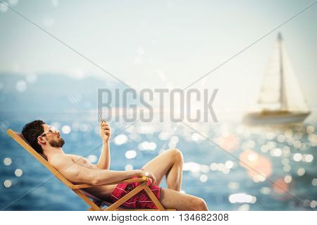 Man with sunglasses and cellphone at sea on deckchair