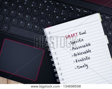 Handwriting SMART Goal on blank notebook with laptop keyboard background (Selective Focus)