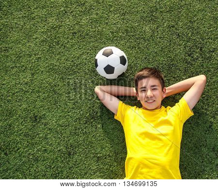 Happy Teenage Boy With A Soccer Ball Lying On The Green Lawn