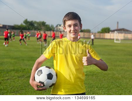 Happy Teenage Boy With A Soccer Ball In His Hand Against The Background Of The Stadium. Training