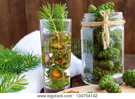 Young green fir cones on the wooden background. For making medicinal infusion.