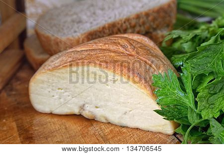 Piece of cheese bread and greens on a wooden table. Indoors. Blackout at the edges. Horizontal format. Color. Photo.