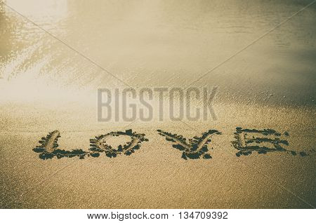 Love text wrote on beach sand near sea wate vintage instagram toned image
