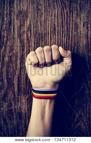 closeup of a young caucasian man with a band patterned as the rainbow flag tied to his wrist and his fist raised against a rustic wooden background