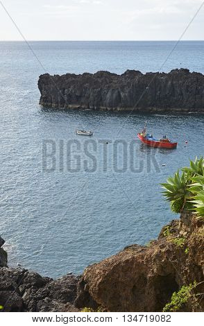 Fishing boats moored near harbour entrance at Camara de Lobos in Madeira Portugal