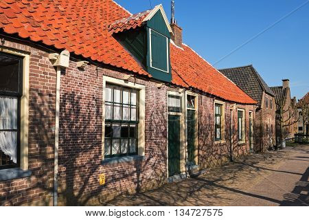 Single-storey dutch houses on the street of the  open-air museum in Enkhuizen, The Netherlands