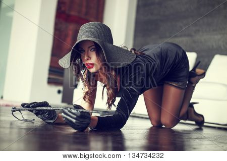 Sexy rich woman in hat and whip kneeling on floor indoor