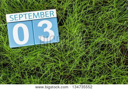 September 3rd. Image of september 3 wooden color calendar on green grass lawn background. Autumn day. Empty space for text.