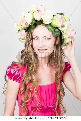 Beautiful young leggy blonde in a little red dress on head a wreath of flowers, rope wrapped vine and ivy.