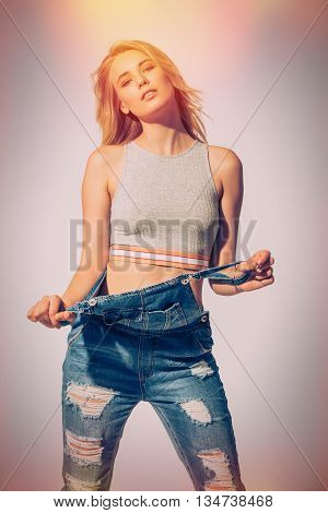 Casually beautiful. Studio shot of beautiful young woman taking off her jeans overall and looking at camera