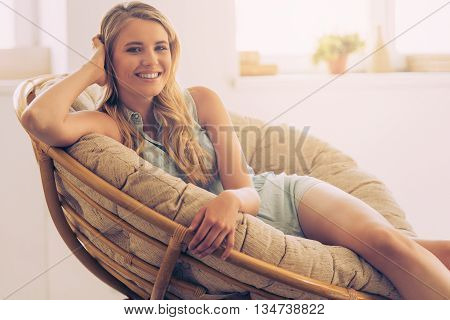 Feeling carefree and relaxed. Beautiful young woman looking at camera and smiling while sitting in big comfortable chair at home