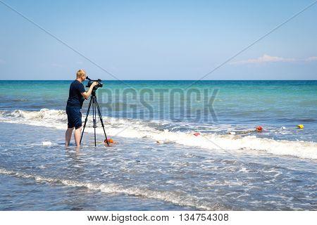 Odesa, Ukraine - June 4, 2016: TV camera man filming a beach sport event, windsurfing competition
