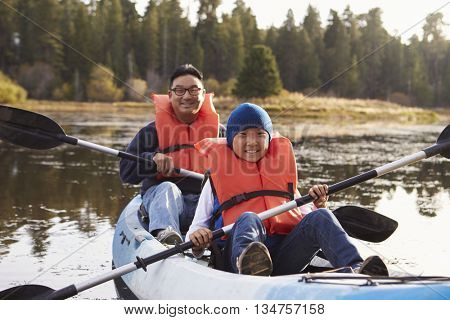 Father and son kayaking on a rural lake, front view