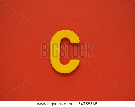 Capital letter C. Yellow letter C from wood on red background.