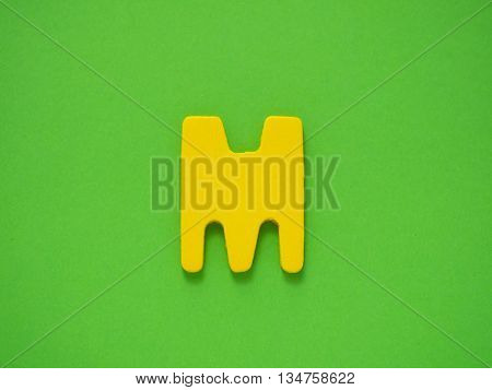 Capital letter M. Yellow letter M from wood on green background.