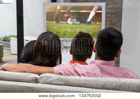 Happy family watching tv on the sofa against football players tacakling for the ball on pitch