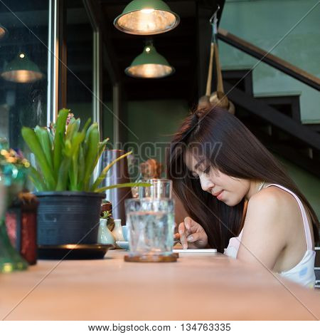 lifestyle of women using a mobile phone in cafe coffee shop with texting message on app smartphone playing social network