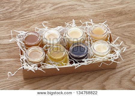 A paper box with eight different kinds of honey decorated with sawdust. poster