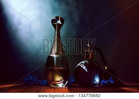 two bottles of perfume in a dark background