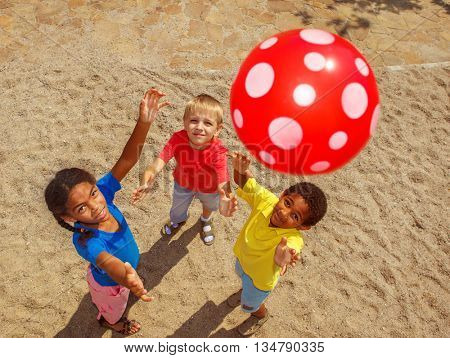 Group of school aged kids playing with a ball outside