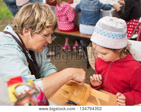 ST. PETERSBURG RUSSIA - JULY 26 2015: Unidentified girl learns to weave bast basket on a city fair. Master class teaching children folk crafts weaving a basket