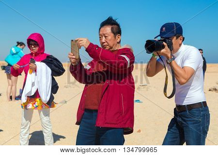 PARADISE ISLAND, EGYPT - FEBRUARY 12, 2016: Chinese tourist taking photos at the beach.