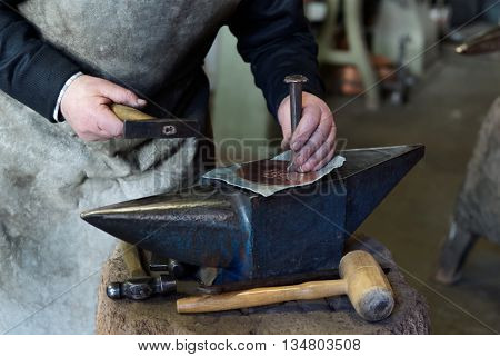 Old smith is chieseling a copper sheet in workshop, making pattern