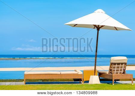 Sun umberella & daybeds overlooking beautiful tropical beach in Bali on a perfect sunny day.