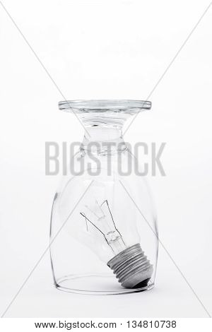An upside down drinking glass confining a lightbulb on a white background.