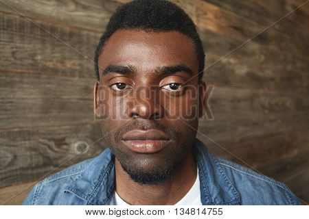Close Up Portrait Of Dark-skinned Man Looking Seriously At Camera On Wooden Background. Thoughtful A