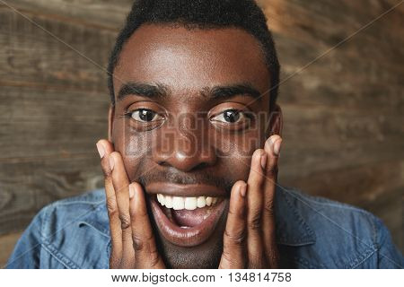 Happy And Amazed African American Male Looking Exuberantly At Camera With Hands On Cheeks And Mouth