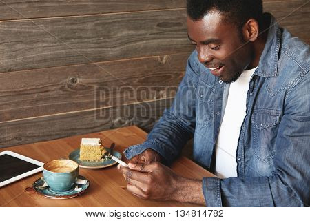 Cheerful African Man In Denim Shirt Is Happy About Good News From The Net. This Guy Is Sitting Alone