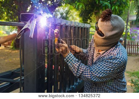 Unidentified hooded man welding steel platform bright light and sparks outdoor with blurr background trees