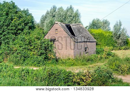 Old barn with collapsed roof of corrugated sheets made with asbestos. The photo was taken shortly before the total demolition of the building.