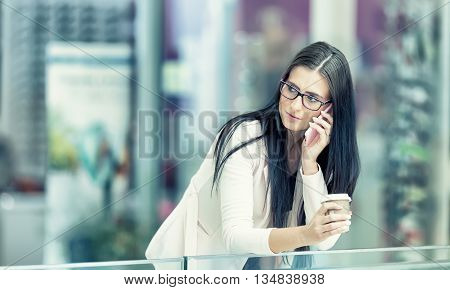 Portrait of young attractive business woman standing in the shopping mall with coffee and using her cell phone. Business break. Coffee break.