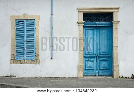 Photo of typical Cypriot old aged white building with bright blue wooden door window with closed shutters and rainwater pipe
