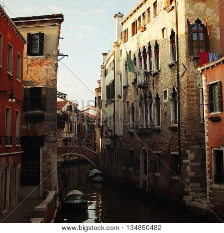 Evening in Venice. Small canal and houses. Aged photo. Street buildings. Toned image. Channels of Venice. Retro filter photo. Italy.