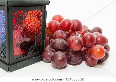 Red grapes and Ramadan lantern on white background. Ramadan Eid concept background