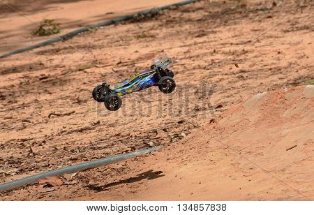 Sydney, Australia - November 30, 2014. Radio controlled buggy car model in race, internal combustion engine on a bumpy red clay road. (St Ives Showground, Sydney, Australia)
