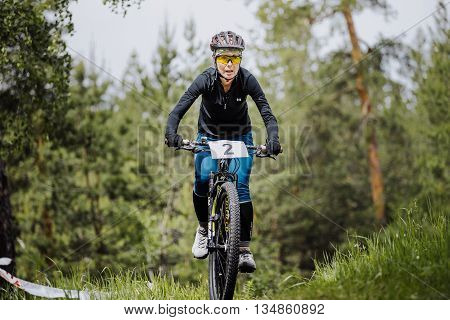 Chelyabinsk Russia - June 5 2016: young girl athlete cyclist rides through forest during cross-country race
