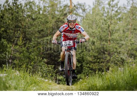 Chelyabinsk Russia - June 5 2016: male athlete a cyclist uphill in forest during cross-country race