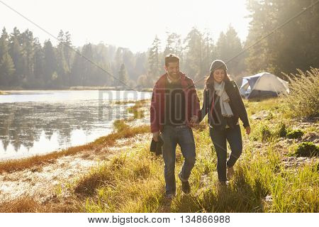 Happy couple on camping trip walk near a lake holding hands