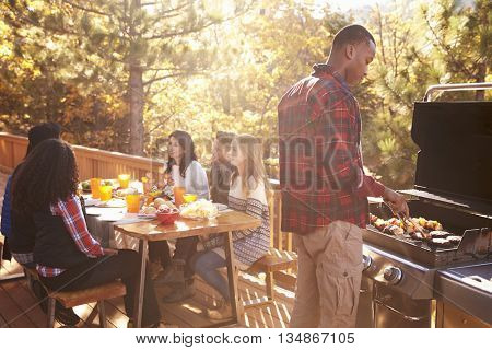 Man barbecues for friends at a table on a deck in a forest