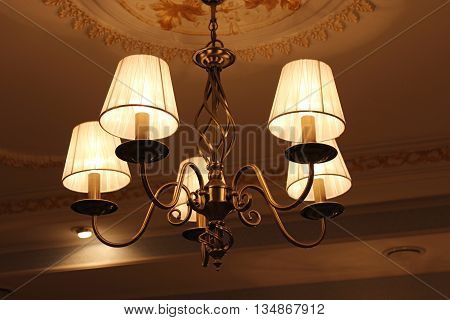 Beautiful chandelier under the top with romantic standard lamps