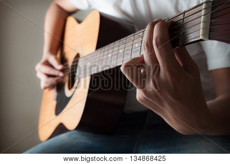 Man in white t-shirt playing acoustic guitar