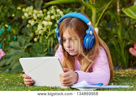 Blond kid girl with tablet pc lying on grass turf with headphones